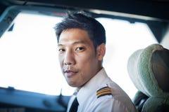Retrato de um piloto masculino que senta-se na cabina do piloto foto de stock