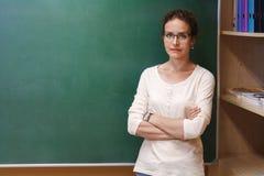 Retrato de um professor fêmea perto do quadro-negro da escola Foto de Stock