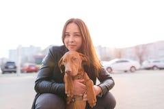 Retrato de um proprietário do cão e de uma menina na perspectiva do por do sol Uma caminhada com um animal de estimação na cidade fotografia de stock