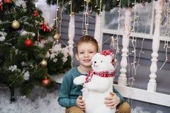 Retrato de um rapaz pequeno bonito que abraça um urso de peluche macio imagens de stock royalty free