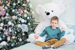 Retrato de um rapaz pequeno bonito que abra?a um urso de peluche macio fotos de stock