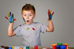 Retrato de um rapaz pequeno bonito que joga messily com pinturas Fotos de Stock Royalty Free