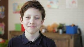 Retrato de um rapaz pequeno bonito que ri olhando a câmera que tem o divertimento filme