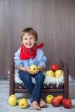 Retrato de um rapaz pequeno feliz, comendo as maçãs, sentando-se em um bebê Foto de Stock