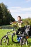 Retrato de um rapaz pequeno que monta um triciclo no parque imagens de stock royalty free