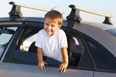 Retrato de um rapaz pequeno de sorriso na praia no carro Imagem de Stock Royalty Free