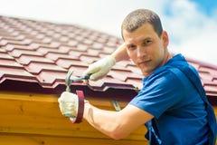 Retrato de um reparador masculino contratado em reparar um telhado de uma casa imagens de stock
