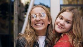 Retrato de um riso caucasiano novo de dois amigos das mulheres feliz na câmera que abraça-se que aprecia o estilo de vida relaxad vídeos de arquivo
