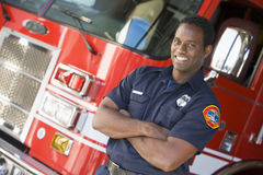 Retrato de um sapador-bombeiro por um motor de incêndio Fotografia de Stock Royalty Free