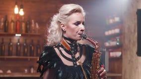 Retrato de um saxofonista fêmea novo que executa uma música na frente de um contador da barra filme