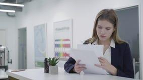 Retrato de um secretário ou de uma mulher de negócio em um negócio que olha o terno de papel com cartas com relatórios na pro vídeos de arquivo