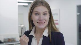 Retrato de um secretário ou de uma mulher de negócios satisfeita, feliz, satisfeita em um terno apertado do negócio que olha a vídeos de arquivo