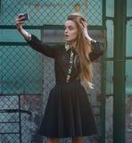 Retrato de um selfie bonito da jovem mulher no parque com um smartphone que faz o sinal de v Foto de Stock Royalty Free