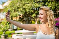 Retrato de um selfie bonito da jovem mulher no parque com uma manutenção programada Fotos de Stock