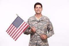 Retrato de um soldado novo de sorriso com bandeira americana foto de stock royalty free