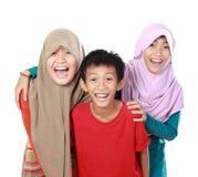 Retrato de um sorriso de três crianças Fotografia de Stock Royalty Free