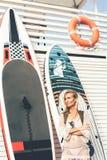 Retrato de um surfista com placas do SUP próximo pela parede de madeira branca imagem de stock