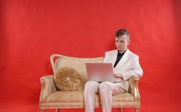 Retrato de um terno branco vestindo e do assento do escritório do homem do jovem adolescente no sofá luxuoso dourado no fundo ver fotos de stock