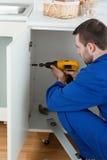 Retrato de um trabalhador manual que repara uma porta Foto de Stock