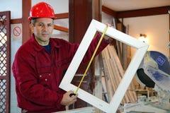 Retrato de um trabalhador que usa uma fita métrica Fotos de Stock