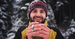Retrato de um turista novo com um chá bebendo da cara bonita do copo do ferro no meio da montanha, congelou-se filme
