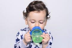Retrato de uma água potável bonito da criança da garrafa Imagens de Stock Royalty Free