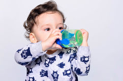 Retrato de uma água potável bonito da criança da garrafa Fotografia de Stock