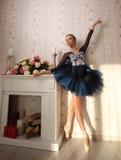 Retrato de uma bailarina na luz do sol no interior home Conceito do bailado fotografia de stock
