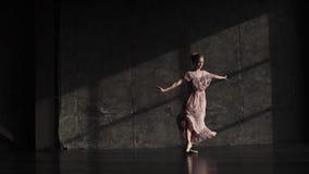 Retrato de uma bailarina nos pointes que dançam o balé clássico em um fundo escuro no estúdio Movimento lento video estoque