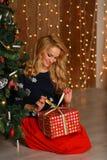 Retrato de uma caixa de presente de sorriso e de abertura feliz da mulher Ano novo feliz! Fotos de Stock Royalty Free