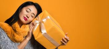Retrato de uma caixa de presente bonita de sorriso da terra arrendada da menina isolada sobre o fundo amarelo fotografia de stock