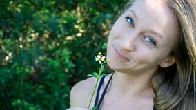 Retrato de uma cara loura normal caucasiano nova da mulher com os olhos verdes azuis que sorriem com uma flor da margarida na nat imagem de stock royalty free
