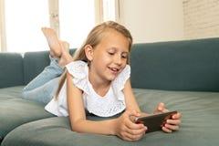 Retrato de uma criança bonita que encontra-se no sofá em casa que sorri e que joga com telefone celular imagem de stock