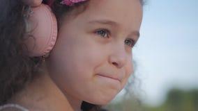 Retrato de uma criança bonito com cabelo encaracolado, menina caucasiano em um vestido cor-de-rosa com uma flor cor-de-rosa em su filme