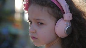 Retrato de uma criança bonito com cabelo encaracolado, menina caucasiano em um vestido cor-de-rosa com uma flor cor-de-rosa em su video estoque