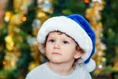 Retrato de uma criança esperta em um chapéu azul de Santa, close-up no sim novo fotografia de stock royalty free