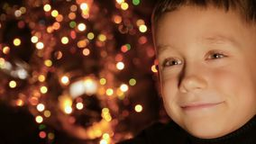 Retrato de uma criança no fundo de luzes de Natal vídeos de arquivo