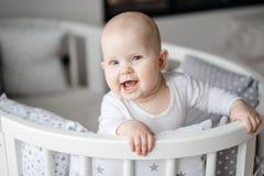 Retrato de uma criança que fica em no seu berço e sorriso de bebê foto de stock