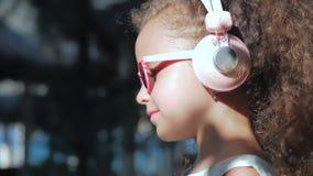 Retrato de uma crian?a bonito, de uma menina bonita pequena maravilhosa em um vestido branco com vidros cor-de-rosa e de fones de vídeos de arquivo