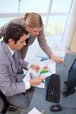 Retrato de uma equipe focalizada do negócio que olha um gráfico Imagens de Stock Royalty Free