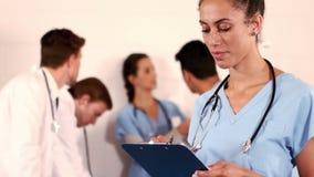 Retrato de uma escrita da enfermeira em sua prancheta vídeos de arquivo