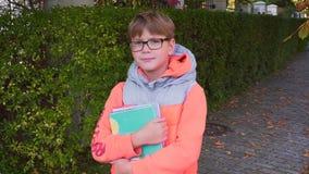 Retrato de uma estudante que que está com um livro de texto à disposição, sorrindo e olhando a câmera O fim do verão, vídeos de arquivo