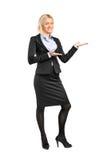 Retrato de uma fêmea no terno que gesticula a boa vinda Fotografia de Stock