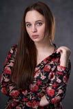 Retrato de uma f?mea em um vestido colorido no fundo cinzento fotografia de stock royalty free