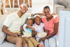 Retrato de uma família de quatro pessoas que olha a tevê foto de stock
