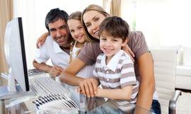 Retrato de uma família de sorriso em um computador fotografia de stock royalty free