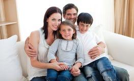 Retrato de uma família de sorriso que senta-se no sofá Imagem de Stock