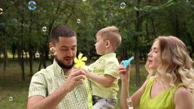 Retrato de uma família feliz com um filho pequeno no parque com bolhas de sabão Mo lento vídeos de arquivo