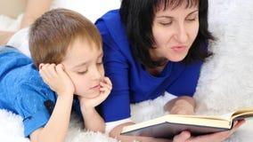 Retrato de uma família feliz A mãe lê um livro a sua criança Close-up filme