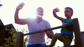 Retrato de uma família feliz, pai que joga com seu filho, acenando uma mão no luminoso, olhando o divertimento de sorriso da câme filme